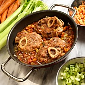 Osso buco with celery and carrots in a stew pot