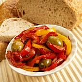 Peperonata (rote und gelbe Paprika, grüne Oliven, Knoblauch) mit Brot