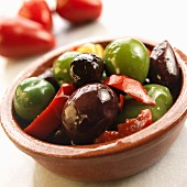 Marinated olives and peppers in a terracotta dish