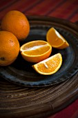 Oranges, whole and sliced, on a plate