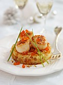 Scallops with salmon caviar on a potato cake for Christmas