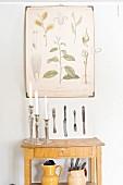 Kerzenständer auf schlichtem Wandtisch, darüber Tafel mit botanischer Zeichnung