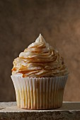 A vanilla cupcake topped with caramel icing and caramel syrup