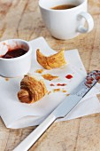 A croissant, jam and a cup of coffee