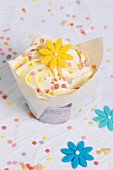 A cupcake decorated with a sugar flower and sugar confetti