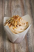 A cupcake topped with buttercream and caramel sauce