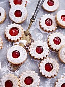 Jammy shortbread biscuits dusted with icing sugar on baking paper