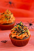 Chocolate cupcakes with orange buttercream and sugar sprinkles for Halloween