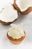 A cupcake topped with coconut cream and grated coconut