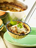 Baked minced meat and cheese soup in a ladle and in a saucepan