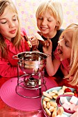 Children eating chocolate fondue