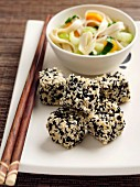 Deep fried diced tofu with a sesame seed coating and rice noodles with vegetables