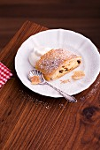 A slice of apple strudel with icing sugar and cream