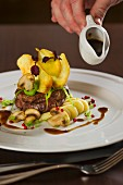 Gravy being poured over beef fillet with potato crisps and mushrooms