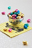 Chocolate eggs in a silver bowl on a napkin decorated with an Easter bunny
