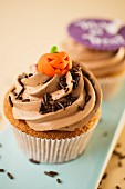 A cupcake decorated with a marzipan pumpkin for Halloween