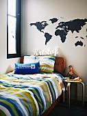 Jugendbett mit gestreiften Bezügen und Holzhocker von Alva Aalto; dekoratives Stickermotiv einer Weltkarte und Namensschriftzug an der Wand