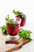 Warm cherry drinks with cinnamon and fresh mint