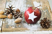 An apple decorated with a star with nuts and pine cones as Christmas decoration