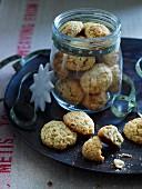 Ingwer-Mandelkekse in einem Schraubglas und auf einem schwarzen Teller