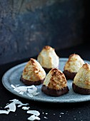 Chocolate-dipped coconut macaroons on a grey plate