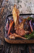 Lamb loin rack joint with roasted carrots in a roasting dish