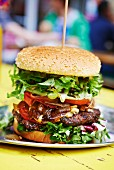 A steak burger with bacon, vegetables and lettuce