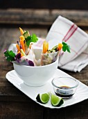 Spring rolls with a vegetable filling, soy sauce and limes
