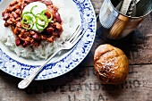 A baked potato and chilli con carne on a bed of rice