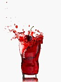 A splashing glass of cherry juice