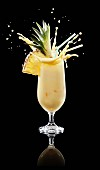 A splashing pina colada in a glass against a black background