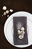 A place setting with a grey napkin decorated with quails eggs