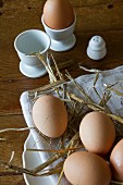 Brown eggs with straw on a plate and in egg cups
