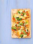 Slices of mozzarella, cherry tomato and basil pizza