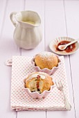 Buchteln (baked, sweet yeast dumplings) in muffin dishes with vanilla sauce and strawberry jam
