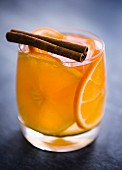 An Old Fashioned cocktail made with whisky, oranges and a cinnamon stick