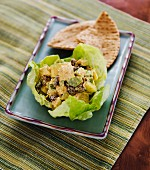 Chicken curry with raisins, apple and celery served in a lettuce leaf served with unleavened bread (India)