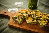 Sliced spinach and goat's cheese frittata on a chopping board