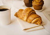 A croissant with a cup of coffee muffins