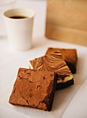 Various brownies with a cup of coffee and a paper bag in the background