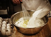 A baker mixing flour and eggs in a bowl