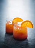 Two Tequila Sunrise cocktails garnished with orange