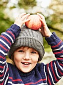 A little girl holding an apple on her head at an autumnal picnic