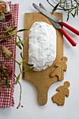 A stollen dusted with icing sugar on a wooden board