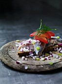 A slice of bread topped with herring and red onions