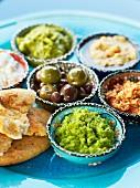 Verschiedene orientalische Dips, Oliven und Fladenbrot