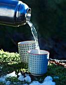 Ingwertee aus Thermoskanne in Becher gießen