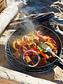 Lemon chicken with pepper in a pan on a barbecue on a beach