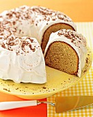 A Bundt cake with vanilla frosting and grated chocolate, sliced