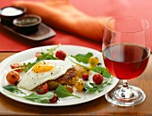 A crab cake topped with a fried egg and served with cherry tomatoes and rocket